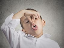 Boy disgust on face pinches nose something stinks Royalty Free Stock Photos