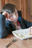 Boy disgusted with junk food. Boy disgusted with pasta and nuggets Royalty Free Stock Photo