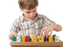 Boy displays wooden figures in form of numerals. Boy in checkered shirt displays wooden figures in form of numerals on table isolated on white background Stock Photo