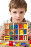 Boy displays wooden figures in form of numerals. Boy in checkered shirt plays in wooden figures in form of numerals isolated on white background Royalty Free Stock Photo
