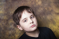 Boy with a distant gaze. Nice image of a seven years old Boy with a distant gaze, studio shot, blurred background Stock Images