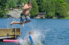 Boy dive bombing friend off dock into lake Royalty Free Stock Images