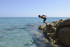 Boy dive into the sea Stock Photos