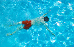 Boy dives in the pool. Boy with red swimming trunks dives in the pool Royalty Free Stock Images