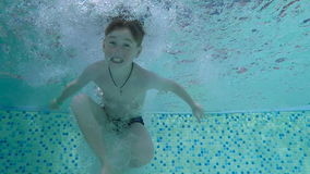 A boy dives into a pool stock video footage