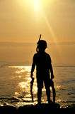 Boy with diving equipment in the sunset Royalty Free Stock Image