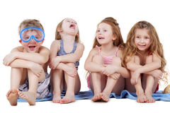 Boy in diving mask and three girls sit on towel Royalty Free Stock Images