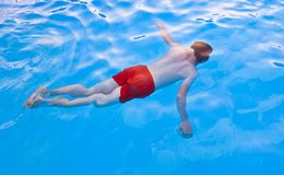 Boy  diving in the pool Stock Images