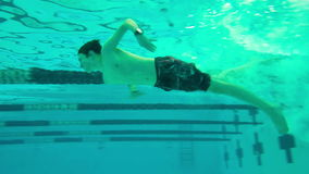 Boy diving into pool, underwater view stock video footage