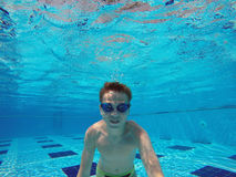 Boy diving into a swimming pool. Cheerful boy diving into a swimming pool Stock Photos