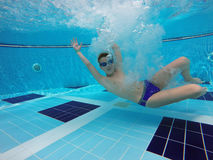 Boy diving into a swimming pool. Cheerful boy diving into a swimming pool Stock Image