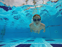 Boy diving into a swimming pool. Cheerful boy diving into a swimming pool Royalty Free Stock Image