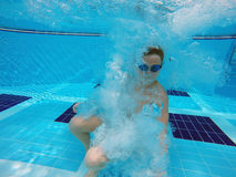 Boy diving into a swimming pool. Cheerful boy diving into a swimming pool Stock Images