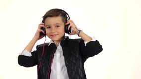 Boy dj wears headphones on head. White background, slow motion stock video