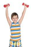 Boy do exercises with dumbbells Stock Photos