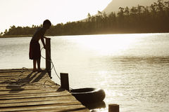 Boy On Dock Pulling In Float Tube Royalty Free Stock Photo