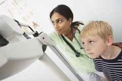 Boy And Doctor Looking At Scale Of Machine. Boy and female doctor looking at the scale of weighing machine in the clinic stock photography