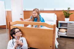 Boy doctor with syringe playing with little girl patient in hospital. Smiling boy doctor with syringe playing with little girl patient in hospital Royalty Free Stock Photo
