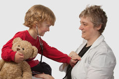 Boy at doctors office. Young caucasian boy and a short hair woman in medical doctor uniform holding a stethoscope on his ear listening to doctor heart beat Stock Photography