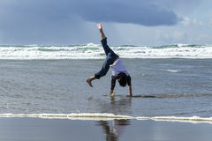 Boy does cartwheel on the beach. Royalty Free Stock Photo