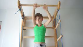 Boy does an exercise on the horizontal bar in the children`s gym at school. Portrait of a boy doing an exercise on the horizontal bar in the children`s gym at stock footage
