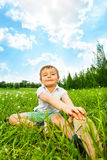 Boy does gymnastics while sitting on a meadow Royalty Free Stock Photo