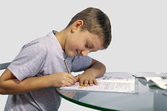 Boy does his homework on a glass table Royalty Free Stock Images