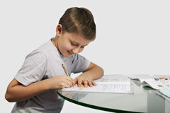 Boy does his homework on a glass table Royalty Free Stock Photography