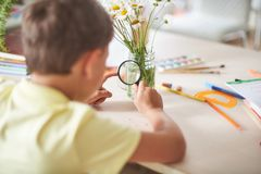 The boy does his homework at home. happy child at the table with school supplies considering through a magnifying glass flower, stock photos