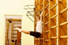 Boy does leg lifts on the monkey bars stock photos