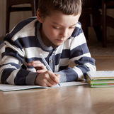 Boy does lessons lying on the floor Royalty Free Stock Images