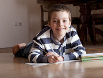 Boy does lessons lying on the floor Stock Image