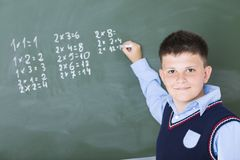 A boy does multiplication on chalkboard royalty free stock photography