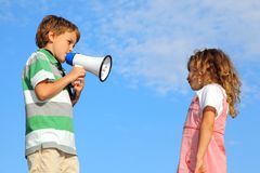Boy does reprimand to girl through loudspeaker Stock Photography