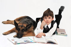 The boy and dog. Lie on a floor and read books Royalty Free Stock Image