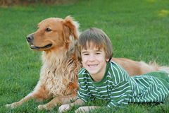 Boy and Dog. Little boy laying down mocking the dog Stock Images