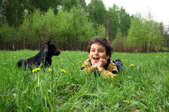 The boy and а dog. Spring walk in a wood. Game with a dog Royalty Free Stock Photo