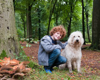 Boy and dog. Cute young boy (7)  and his pet dog posing in an autumn forest scenery Royalty Free Stock Photo