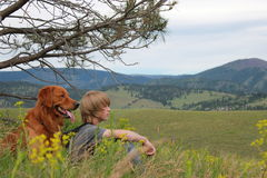 Boy and dog looking into the distance. Boy and dark golden retriever sitting on a hill, looking into the distance Stock Photography