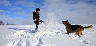 Boy and dog playing in snow stock photography