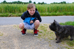 Boy and dog. Boy plays with his cairn terrier Royalty Free Stock Images
