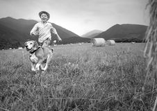 Boy and dog run together on the field with haystacks Royalty Free Stock Photos