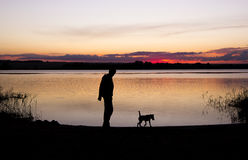 Boy and dog silhouette at sunset lake. Boy is playing with dog at lake during sunset Stock Photography