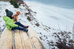 Boy with dog sitting together near frozen lake Royalty Free Stock Images