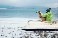 Boy with dog sitting together on the old boat near winter lake Royalty Free Stock Image