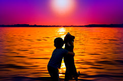 Boy and dog at sunset. Silhouette of boy and dog hugging at sunset Royalty Free Stock Photography