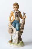 Boy with dog. Vintage statue of boy in yellow jacket, cravat and blue breaches holding straw hat with small dog beside him stock photography