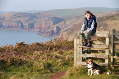 Boy With Dog Walking Along Coastal Path Stock Image