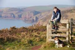 Boy With Dog Walking Along Coastal Path Stock Images