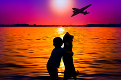 Boy and dog watching aircraft. Silhouette of boy and dog at sunset watching aircraft stock photography